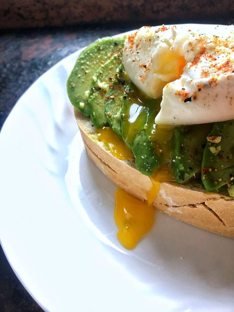 close up of avocado toast seasoned with lemon zest, smoked paprika, salt and pepper, topped with a poached egg with runny yolk running down the avocado and toast