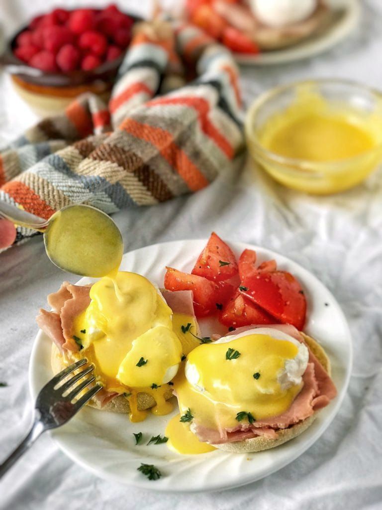 Focus on broken egg Eggs Benedict with a generous flow of Hollandaise and yolk over the ham and English muffin