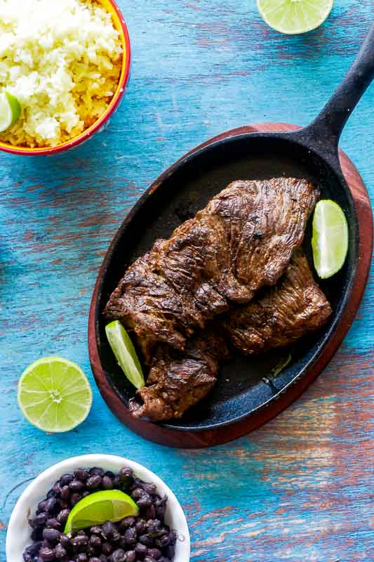 overhead shot of carne asada on a cast iron skillet with black beans, cilantro lime rice and limes
