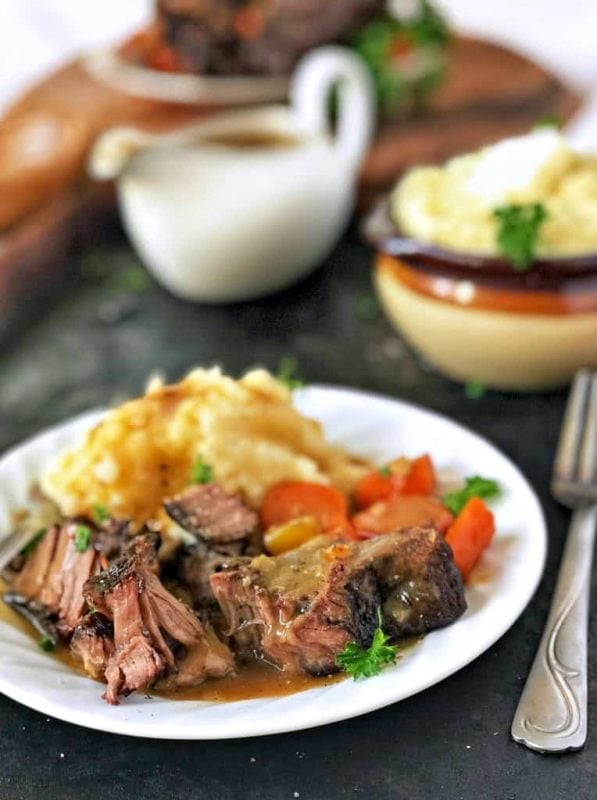 Close up on plate of pot roast with mashed potatoes, gravy, and veggies
