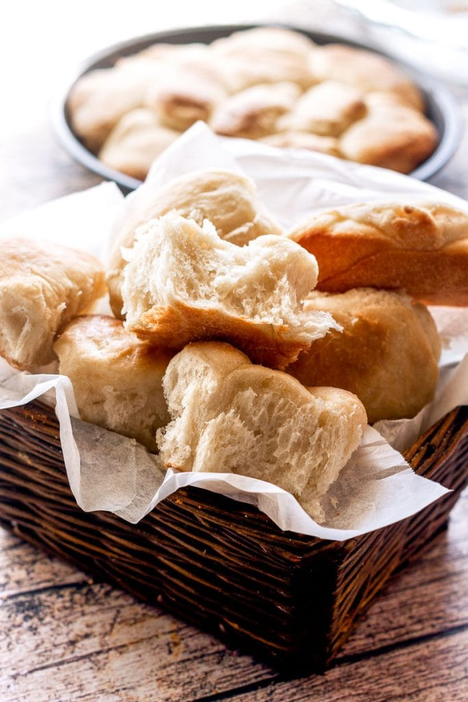 Homemade parker house rolls piled high in a wicker basket with a pan of yeast rolls sitting behind