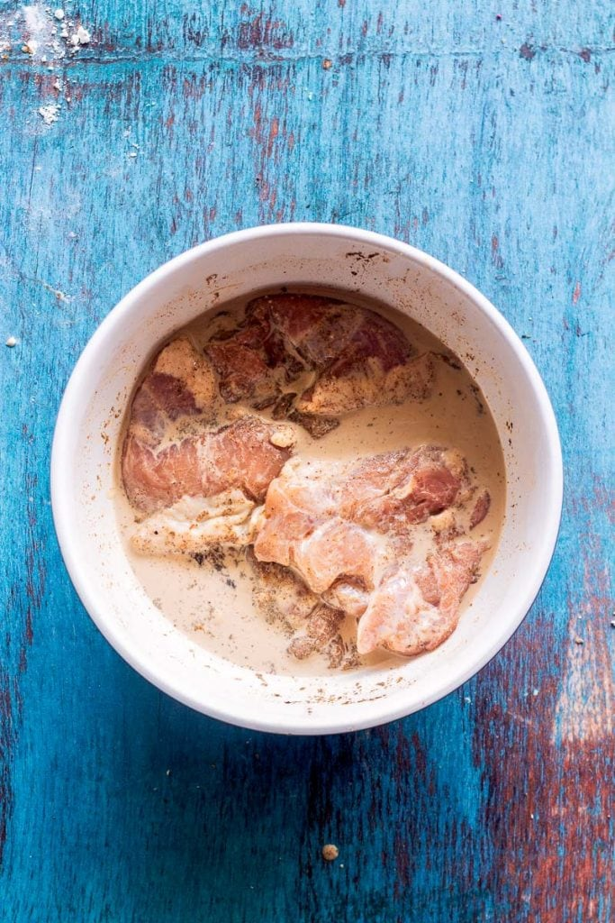 bowl of chicken thighs bringing in buttermilk and spices on a blue wood board