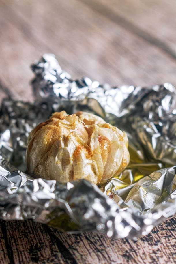 a head of roasted garlic in a pool of olive oil in foil on a wooden table
