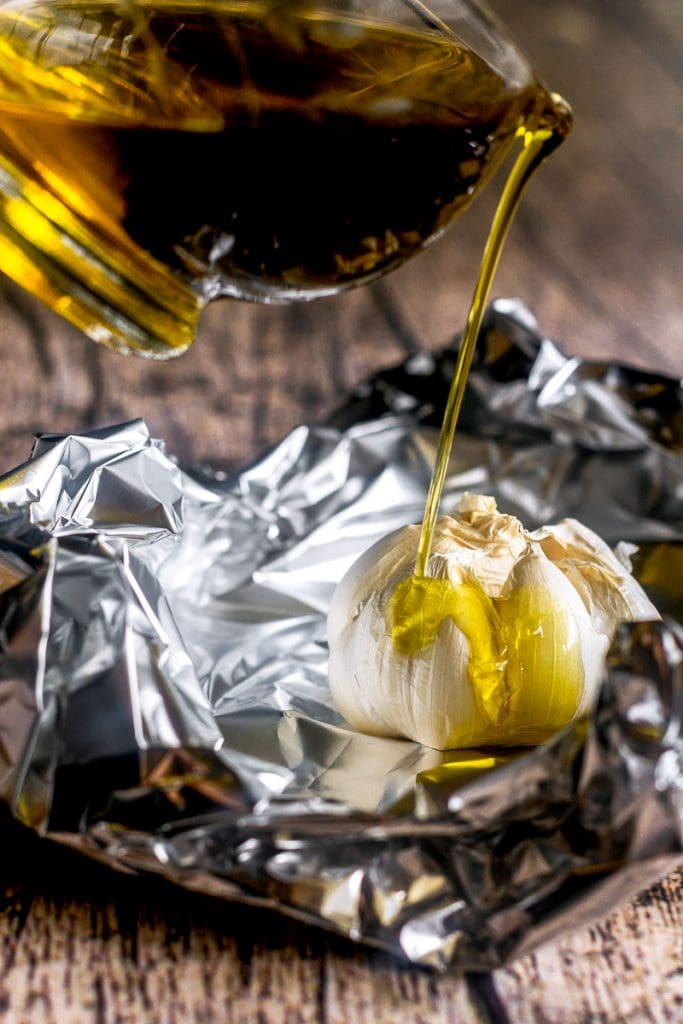 Olive oil being poured over a head of garlic on foil