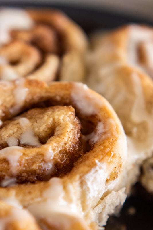 Close up of inside of fluffy cinnamon rolls in pan, drizzled with icing on Sweet Tea and Thyme | www.sweetteaandthyme.com
