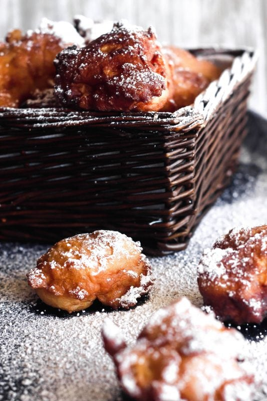Apple Fritters in a basket and scattered on a baking sheet covered in powdered sugar on Sweet Tea and Thyme | www.sweetteaandthyme.com