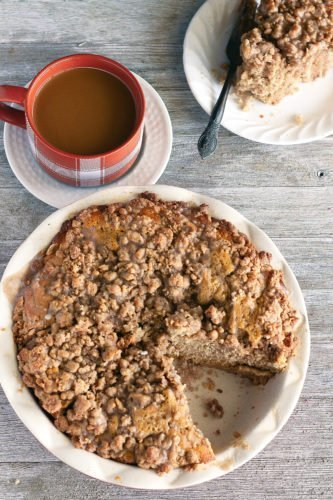Overhead shot of chai latte crumb cake, with a slice served on a plate and a cup of coffee on a wooden table on Sweet Tea and Thyme | www.sweetteaandthyme.com
