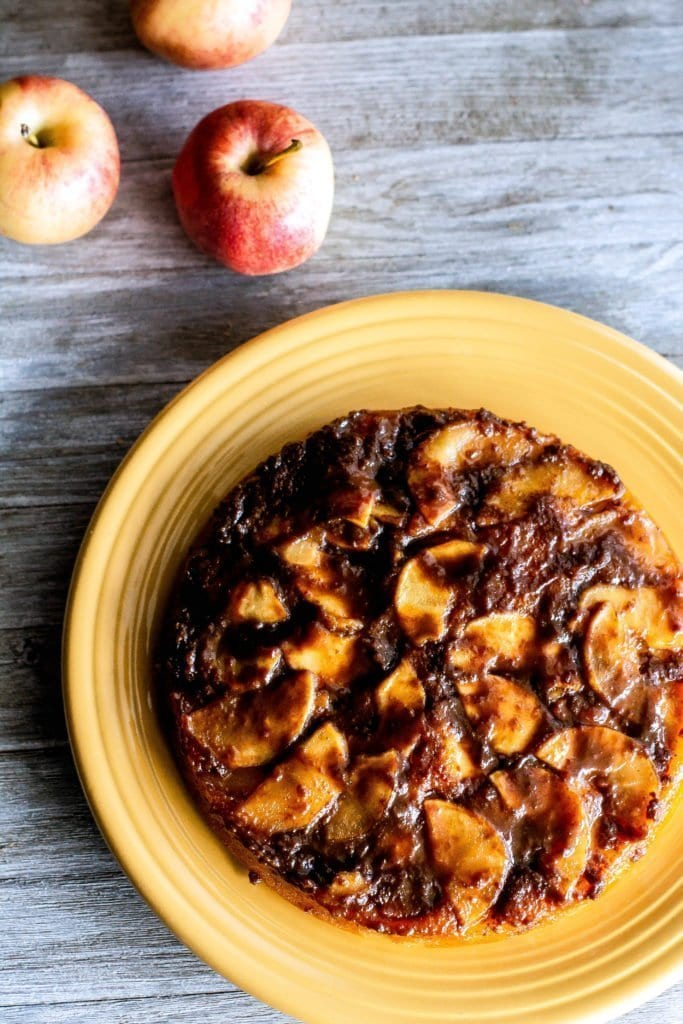 Over head shot of caramel apple upside down cake on wooden board with apples on Sweet Tea & Thyme | www.sweetteaandthyme.com