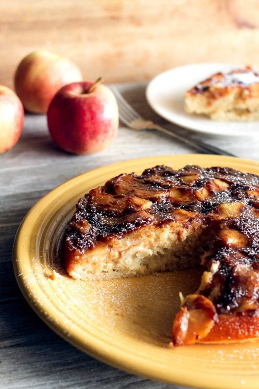 Caramel apple upside down cake on a yellow plate with a slice cut out and served in the background with apples on Sweet Tea and Thyme | www.sweetteaandthyme,com