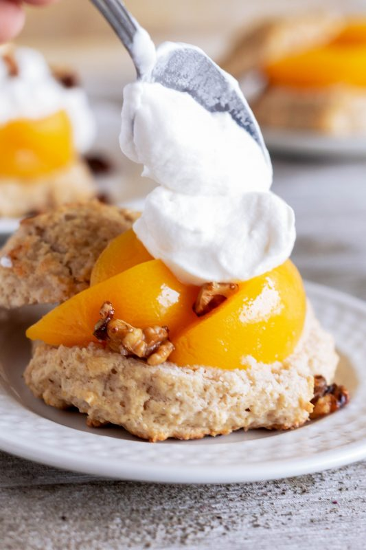 whipped cream being dolloped onto peaches for a peach shortcake
