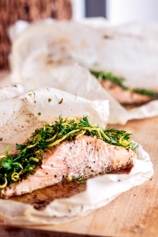 Salmon in parchment paper on wooden board, topped with gremolata