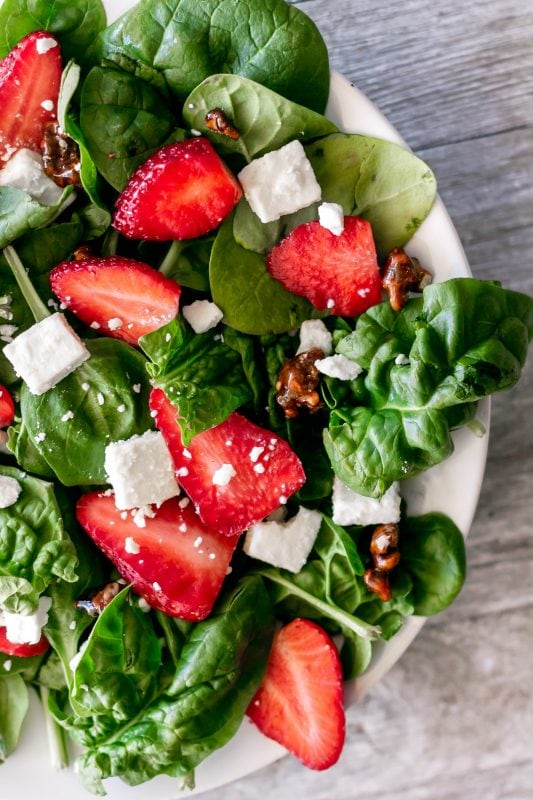 Strawberry spinach salad is delicious and classic with juicy strawberry slices, creamy feta cheese, and crunchy candied nuts with a bright lemon poppy seed dressing!