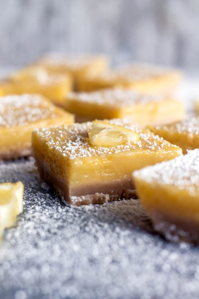 side view of squares of lemon bars, coated in powdered sugar on blue marble
