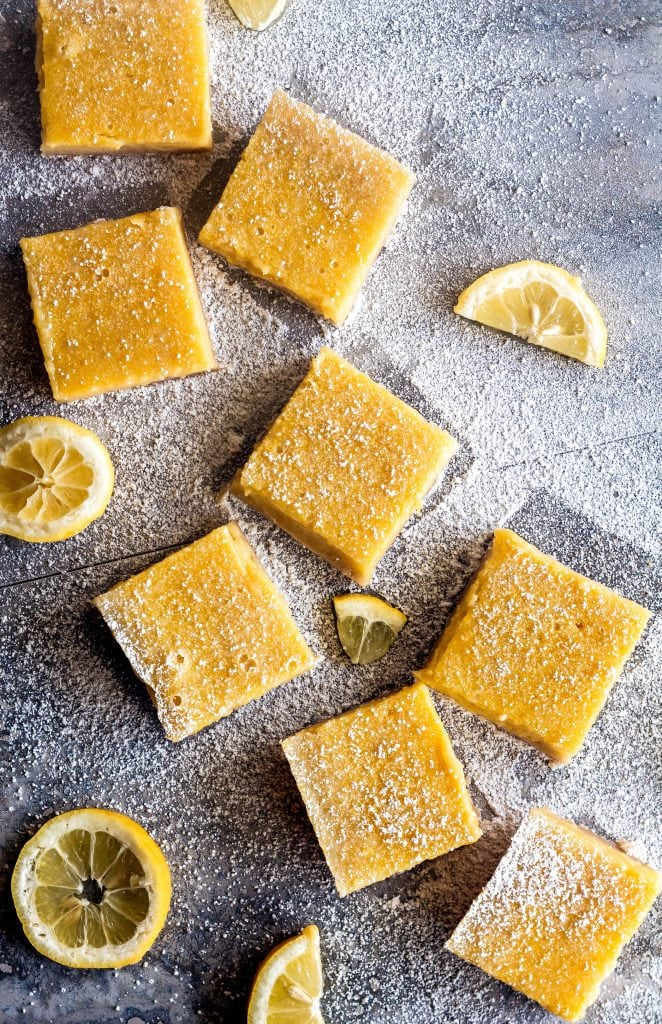 overhead of lemon bar squares, dusted with powdered sugar, with lemon slices strewn on blue marble