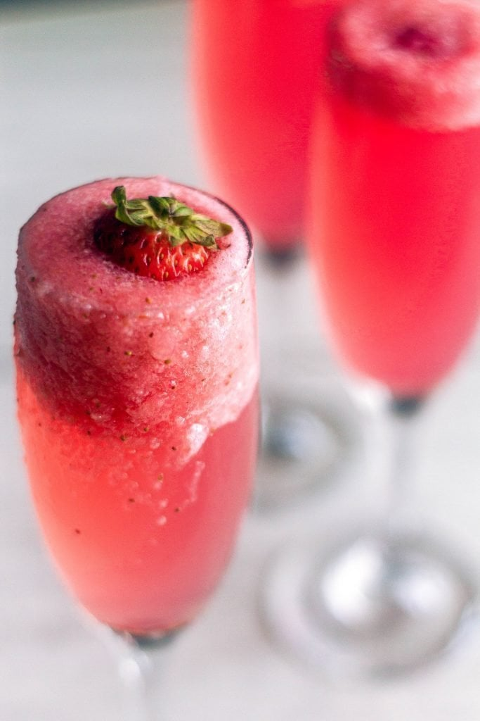 angled shot of strawberry rossini with foam flowing over the champagne flute