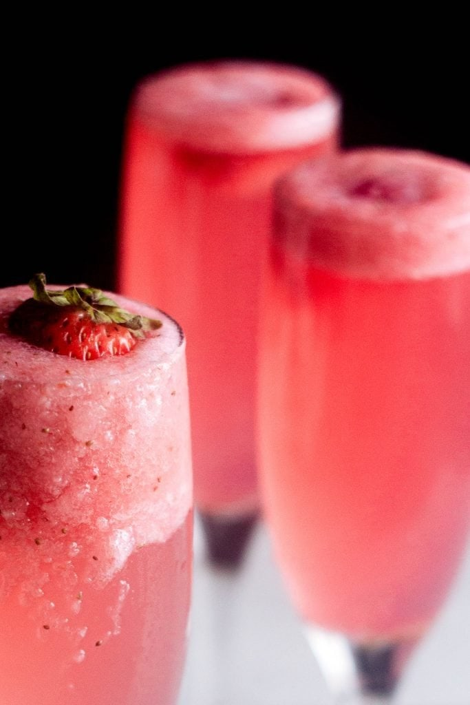 Close up of rossini cocktail with foam and a fresh strawberry in the champagne flute