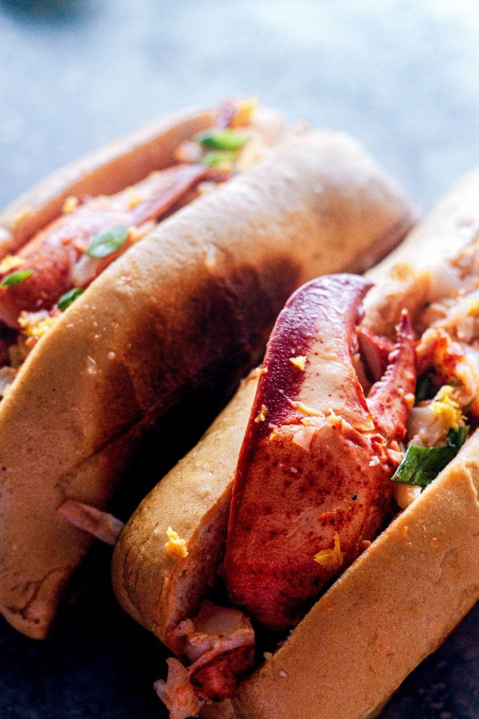 Connecticut-style warm butter lobster rolls are a classic New England summer sandwich. Steamed, shelled, then tossed in drawn butter and dressed with lemon zest and scallions, these are the old-school lobster rolls you've been looking for. #summerrecipes #lobsterrolls #newengland