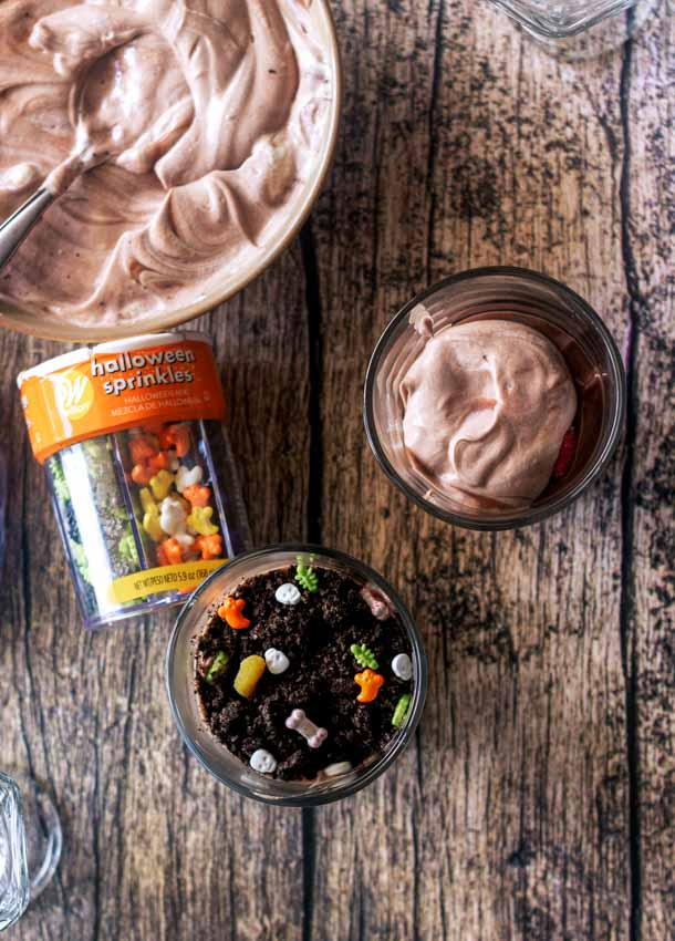 This Ghosts in the Graveyard dessert is quick, fun, and easy enough to let the kids help make them! Chocolate pudding, Oreo cookies, whipped cream, and fun Halloween sprinkles are all you need to make these spooky Halloween party-worthy treats!