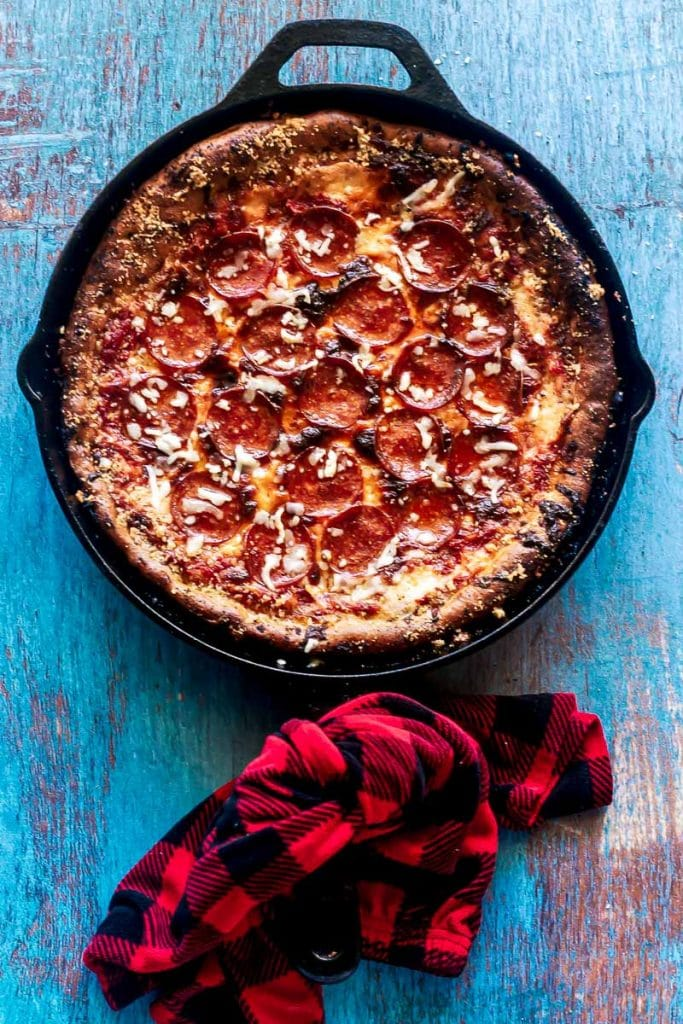 deep dish pizza overhead in cast iron skillet on blue painted wooden table