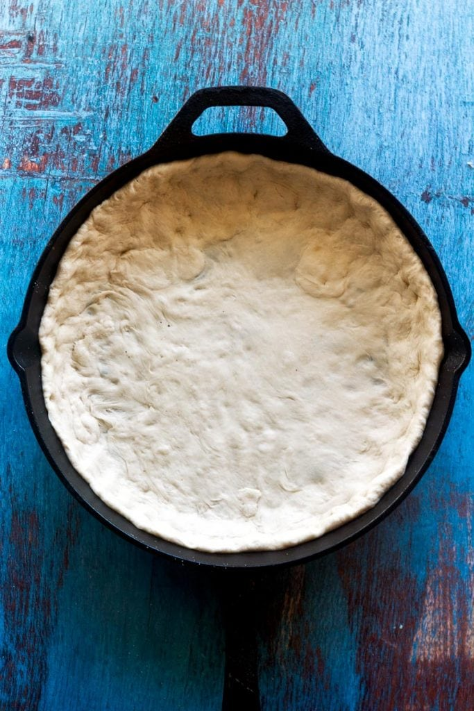 pizza dough that has been fully pressed and stretched for deep dish pizza