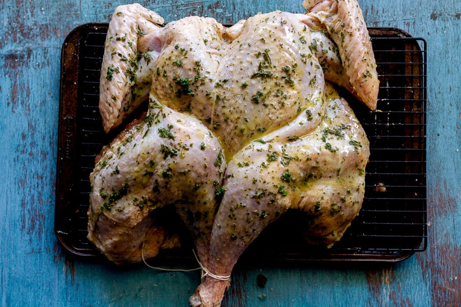 the spatchcock turkey has herb butter brushed over all of the skin to ensure crispiness