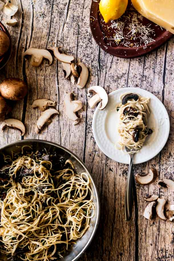 A small plate has a fork with pasta twirled around it. Mushrooms are in the pasta and the pasta has lemon zest and parmesan cheese on it. On the wooden board, a pan of the pasta with creamy garlic sauce sits with mushrooms fallen across the wooden table.