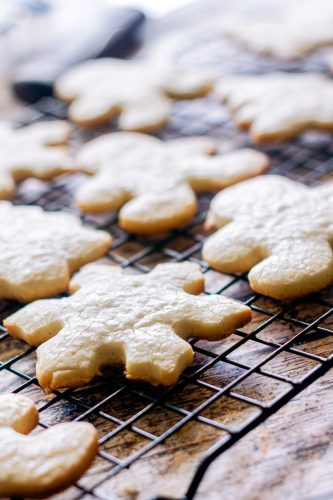 baked Christmas sugar cookies shaped like snowflakes, Christmas trees, and gingerbread men cooling on a wire rack