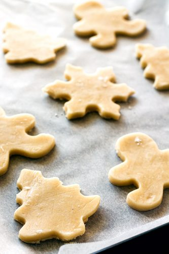 a baking sheet has unbaked Christmas cutout sugar cookies ready for the oven