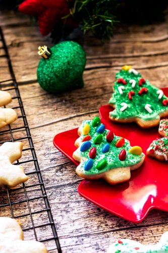 Close up of a decorated sugar cookie Christmas trees on a wood board with ornaments