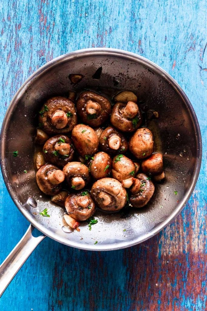 a full view of the pan of button mushrooms sauteed in garlic butter sauce