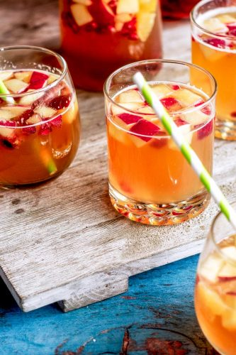 cups of sparkling apple cider sangria sit on a wooden board on blue painted wood table