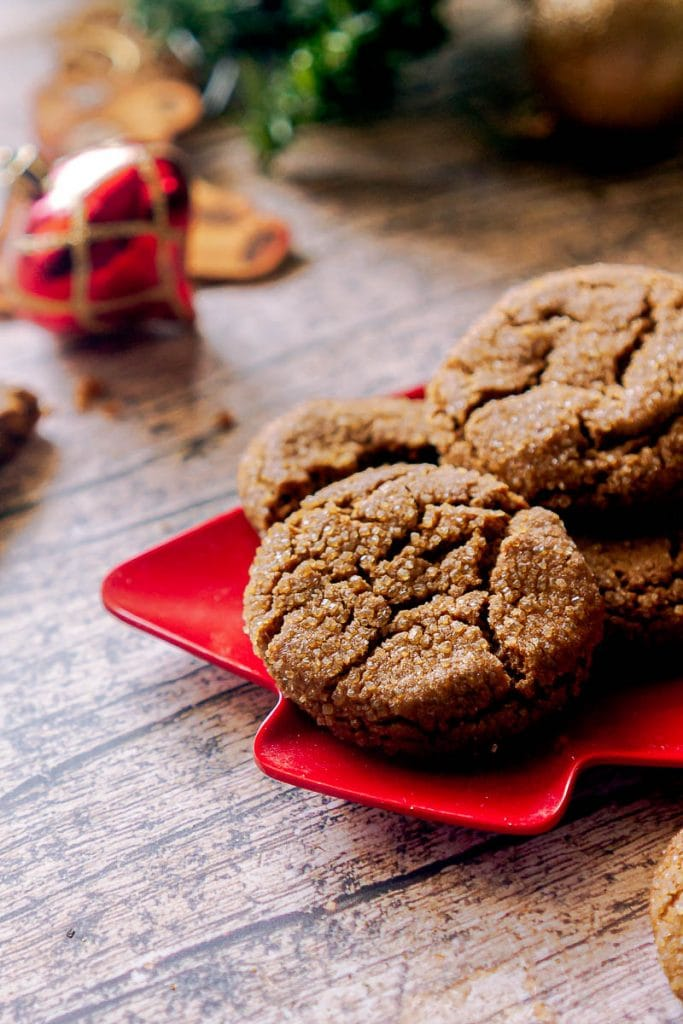Crisp and chewy gingersnap cookies sitting on a red Christmas tree shaped plate on a wooden board