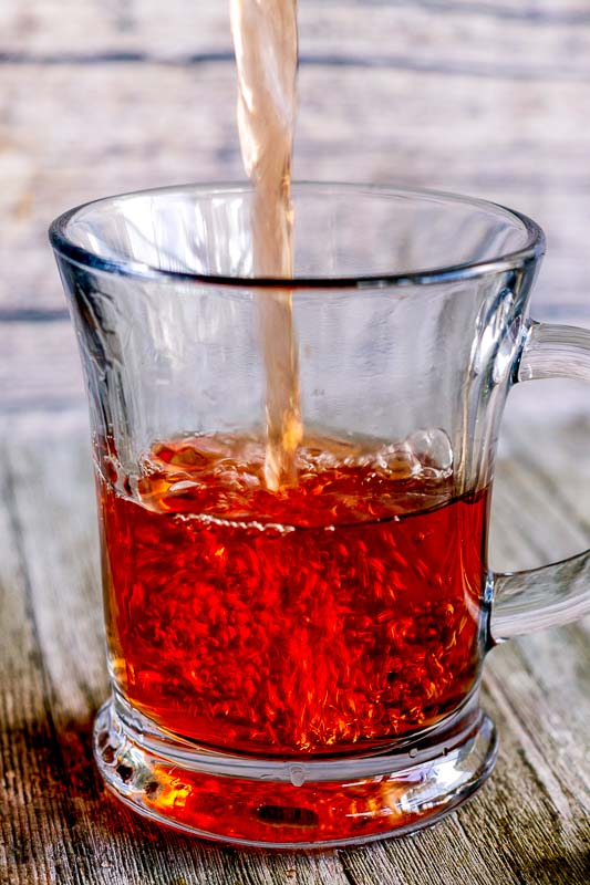hot ginger cinnamon tea being poured into a clear mug