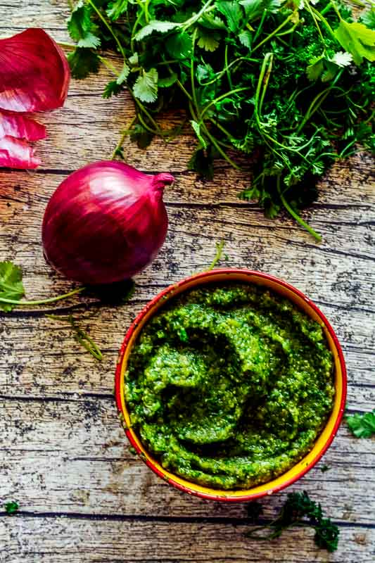 a bowl of bright green caribbean sofrito on a wood table with a red onion and cilantro