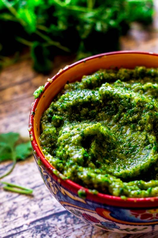 A bowl of homemade puerto rican sofrito on a wood table with cilantro in the background