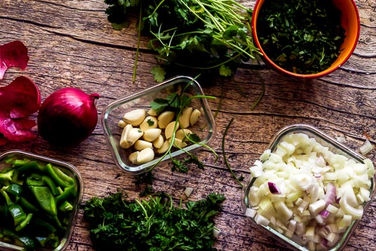 an overhead shot of all the sofrito ingredients: parsley, cilantro, garlic, onions, and peppers all on a wooden table