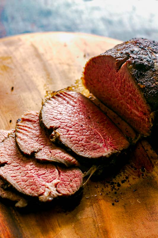 Tender slices of roast beef made in the sous vide on a wood platter