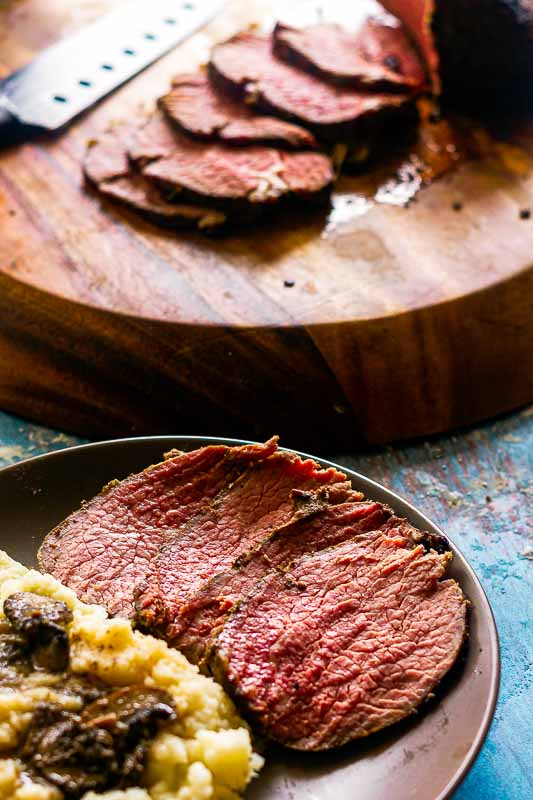 plate of sliced roast beef with mashed potatoes, with wooden platter of roast beef in the background
