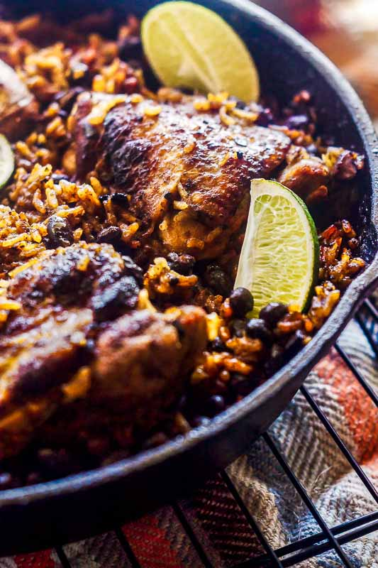 close up of lime, chicken, rice,, and beans in a cast iron pan