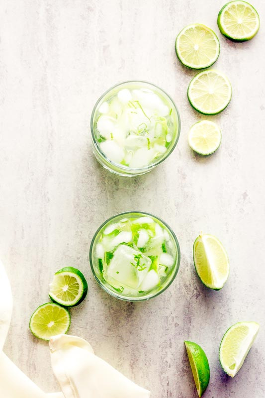 overhead view of two glasses of caipirinha on marble surrounded by lime slices
