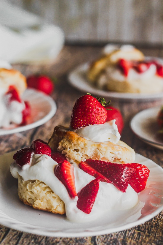 a straight on shot of a strawberry shortcake in front with other shortcakes in back, with softly whipped cream and buttermilk biscuits