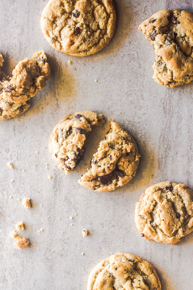 overhead shot of chocolate chip cookies with a few broken in pieces on marble