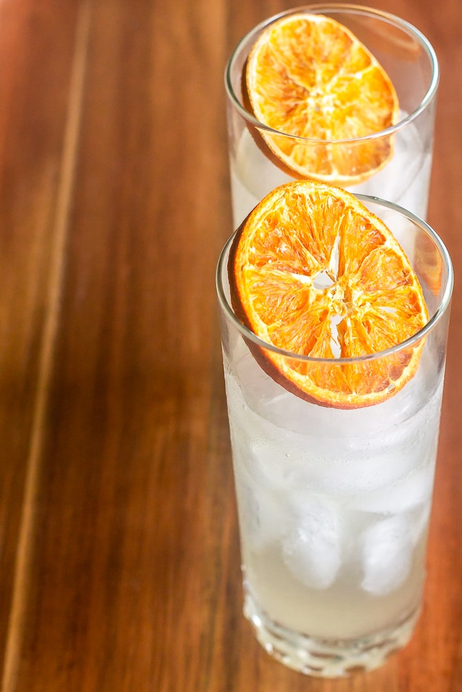 close overhead shot of tom collins drinks garnished with citrus slices
