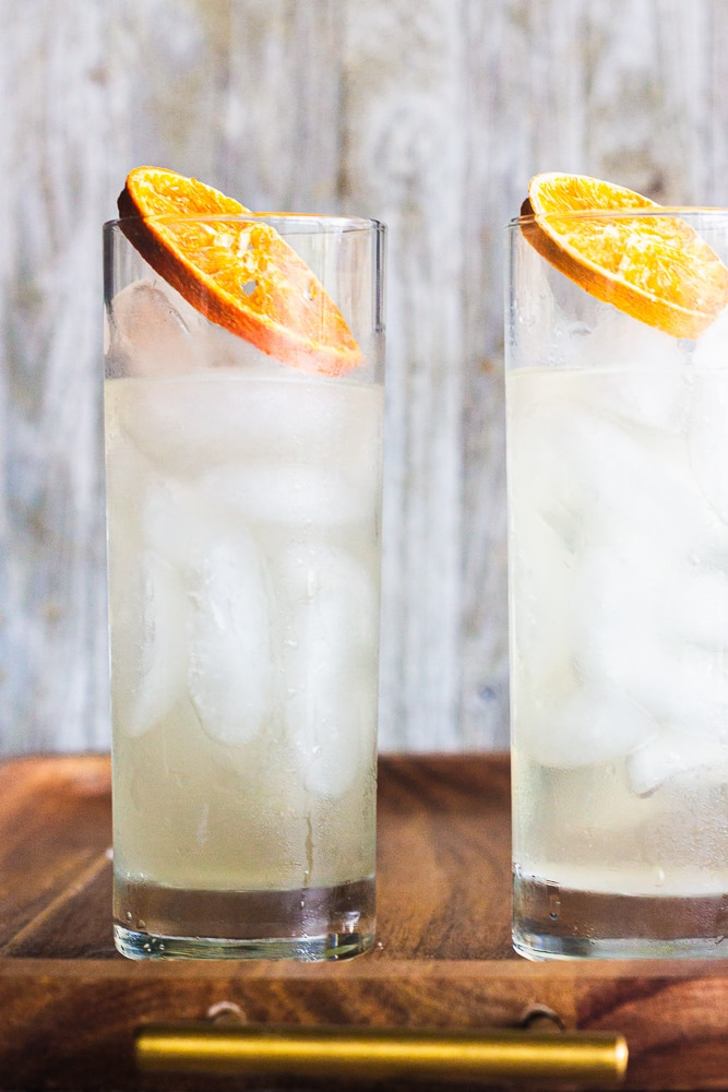 side view of yuzu tom collins drinks with slices of dehydrated oranges.