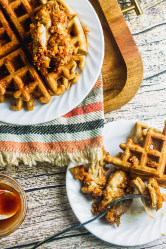 plates of southern style chicken and waffles with honey butter sauce on wood table and platter