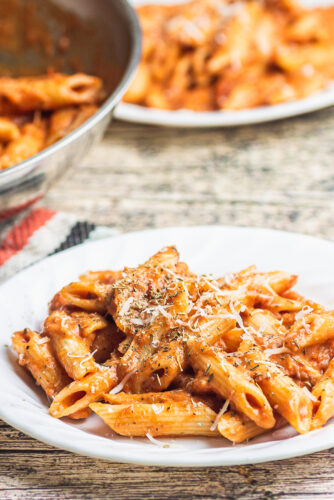 a plate of penne alla vodka is in the foreground with a pan and another plate full of pasta are in the background