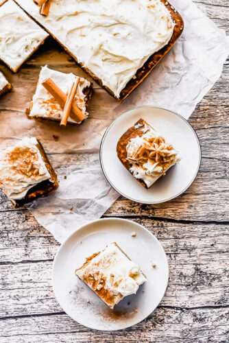 overhead shot of pumpkin sheet cake with slices on parchment paper and plates