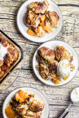 overhead shot of three plates of southern peach cobbler with biscuit topping served with ice cream