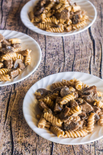 three plates of beef stroganoff with mushrooms served with rotini