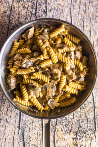 an overhead shot of a skillet full of beef, mushrooms, and stroganoff sauce over rotini pasta
